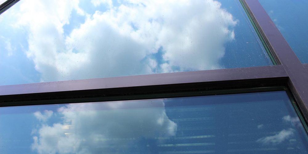 Extreme close up exterior view of large windows at 1939 Building; clouds reflected in the glass