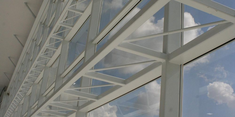Close up of large window wall at Becks Airport; puffy white clouds visible outside