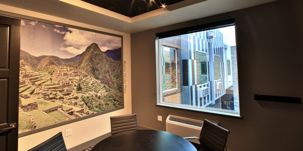 Interior view of conference room with large photo of Machu Picchu and large window looking out at unique exterior windows and courtyard