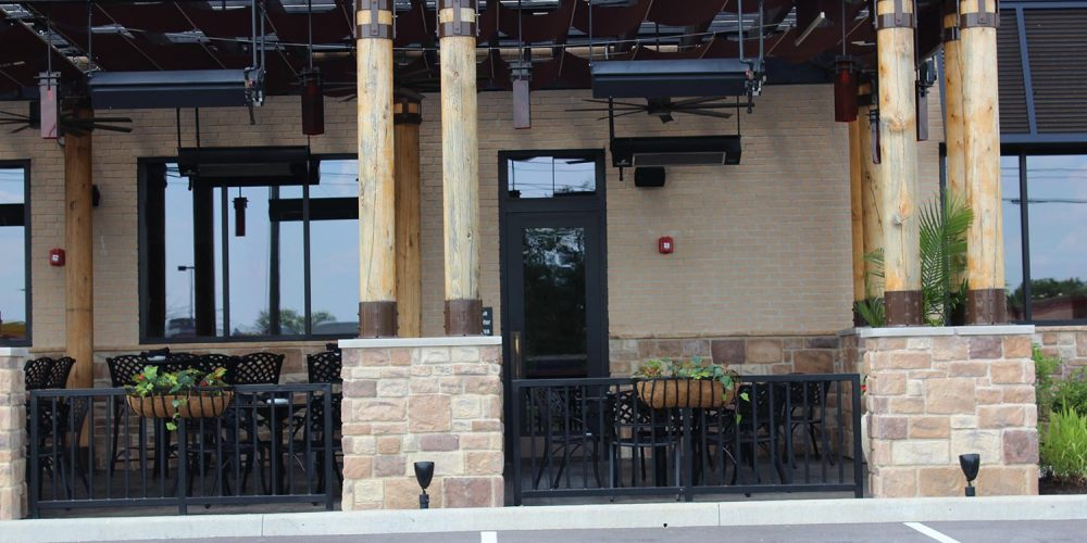 Exterior view of outdoor dining section of Fire Birds; large dark plate glass windows visible